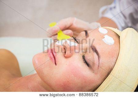 Beautiful woman with facial mask at beauty salon.Pretty woman receiving facial massage