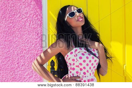 Young attractive smiling african american woman wearing sunglasses