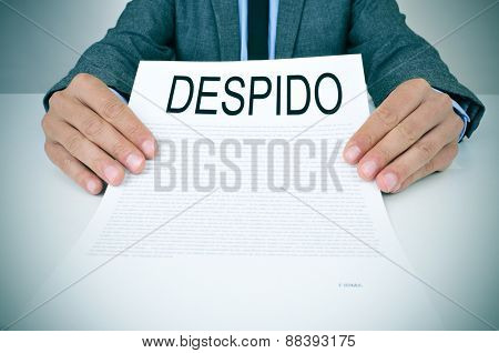 a young caucasian businessman in grey suit sitting at his office desk shows a document with the text despido, dismissal in spanish, written in it
