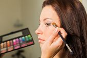 Makeup artist paints the eyebrows model. painting of eyebrows. Makeup artist in a beauty salon doing make-up special brush. Dressing room, fashion, creativity and beauty. poster