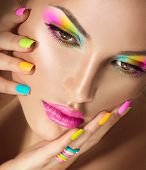Beauty Girl face with Vivid Makeup and colorful Nail polish. Colourful nails. Fashion Woman portrait close up. Bright Colors. Long eyelashes, vivid eyeshadows Rainbow make up poster