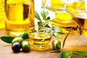 Olive Oil. Pouring Virgin Olive Oil in a bowl close up. Olives and Healthy Olive oil being poured from glass bottle. Diet. Bottle of olive oil. Dieting concept. Healthy food poster