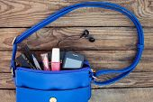Blue women's purse. Smartphone and makeup, from open ladies handbag. poster