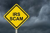 IRS Scam Warning Sign Yellow warning road sign with word IRS Scam with stormy sky background poster