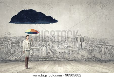 Young businesswoman with colorful umbrella under black cloud