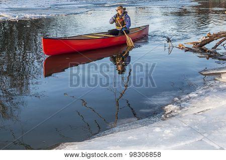 a senior male paddling a red canoe in winter - Cache la Poudre River in Fort Collins, Colorado