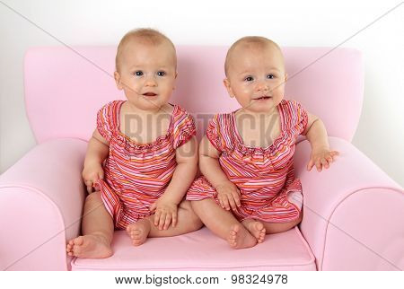 Identical ten month old twin baby girls seated on a pink child size sofa.
