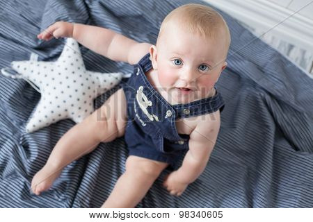 cute baby under a blanket in bed