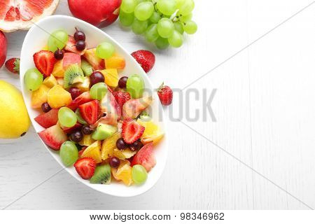 Fresh fruit salad on white wooden table