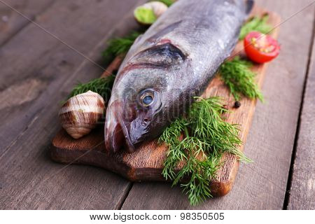 Zander fish and other ingredients on wooden table, closeup