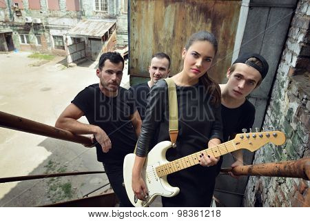 Music band outdoor portrait. Musicians and woman soloist posing outside against grunge yard, black and white.