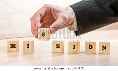 Closeup Of Businessman Creating A Word Mission With Seven Wooden Cubes