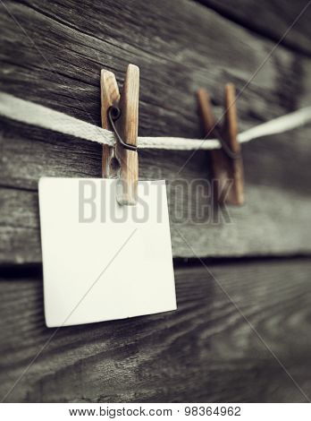 rope with clothespins and a piece of paper against old wood background, place your text here