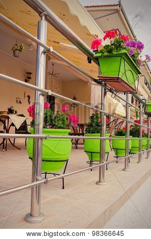 Green Bowls Of Flowers On Yellow House Veranda
