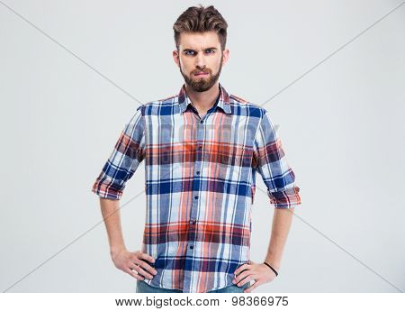 Portrait of a young serious man looking at camera isolated on a white background