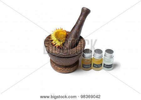 Wooden pounder with bottles of organic oils and flowers