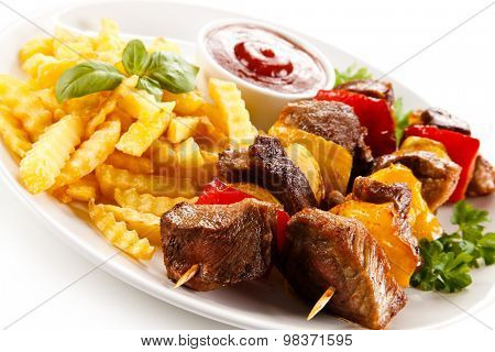 Grilled meat, French fries and vegetables
