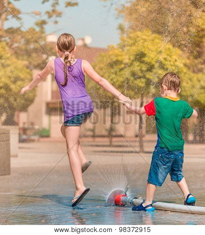 Hot summer in the city - girl and boy are enjoying fountain with cold water