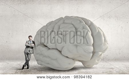 Young businessman leaning on big brain model