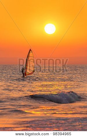 Windsurfer Silhouette At Sea Sunset. Summertime Watersports Concept.