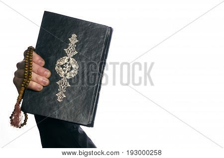 Man's hands holds Koran/ Quran - holy book of muslims and wooden rosary prayer beads isolated on white background with copy space.