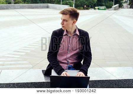 Stylish young man in jacket and jeans sitting and typing on laptop computer outdoors. Technology and communication concept
