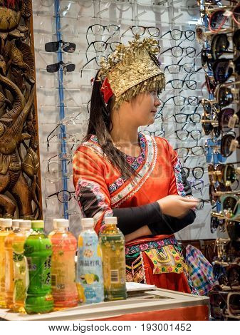 Shanghai, China - Nov 4, 2016: Girl dressed in intricate minority attire behind a shop store. The attire design is typical of one of China's numerous minority racial groups. Low-light image.
