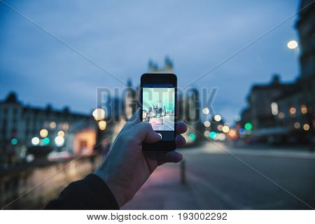 BATH, UNITED KINGDOM - MARCH 8, 2017: Personal Perspective pov of man taking photograph with the mobile phone smartphone of the illuminated cathedral Bath Abbey in Bath United Kingdom