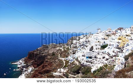 Panoramic view of the village of Oia, Santorini, Greece. Traditional Greek architecture, white houses, the Aegean Sea, the caldera.