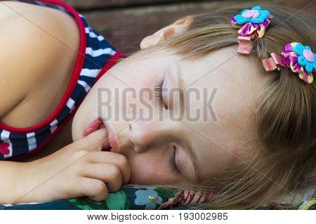 Little pretty girl sleeping sucking thumb and having sweet dreams