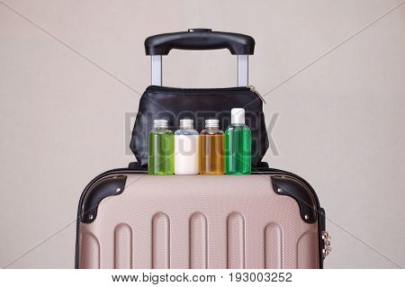 travel toiletries small plastic bottles of hygiene products on the suitcase and cosmetic bag