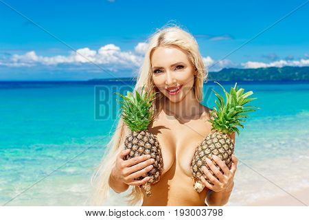 Beautiful blonde with long hair holding two pineapple at the breast on the tropical beach. Summer vacation concept.
