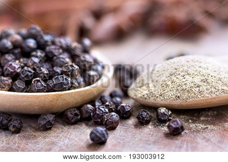 black peppercorns and black pepper powder on wooden spoon.