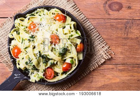 Pasta Tagliatelle with tomato and basil in pan . Top view