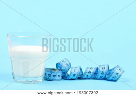 Glass Of Milk Next To Roll Of Blue Measuring Tape