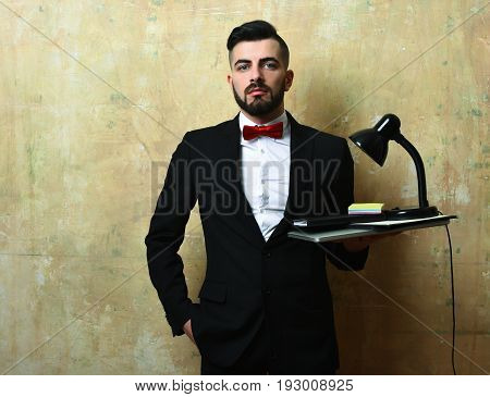 Office Worker With Beard Holds Laptop, Lamp And Stationery