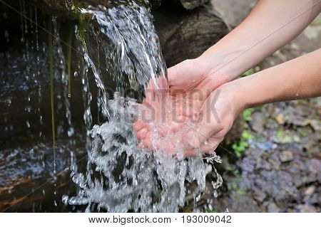 Drinking water and natural water in the hands.