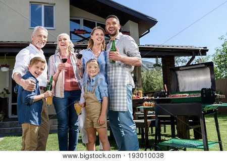 Big Happy Family With Beverages Looking Aside While Having Barbecue Together