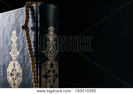 Close-up of Islam holy book of Muslims the Quran/ Koran with prayer rosary beads isolated on black background with copy space.