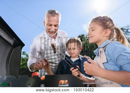 Grandchildren With Grandfather Preparing Sausages On Barbecue Grill Outdoors