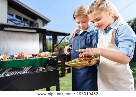 Adorable Children Testing Fresh Meat Just Cooked On Barbecue Grill Outdoors