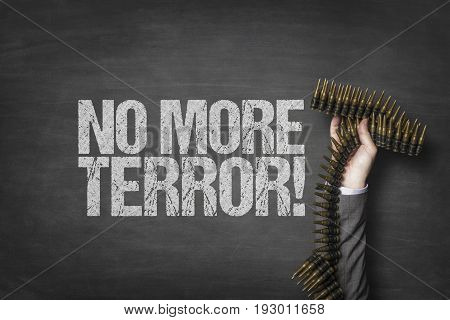 Cropped image of businessman's hand holding bullets by no more terror text on blackboard
