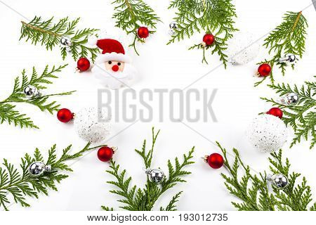 Wide arch shaped Christmas border on white background composed of fresh fir branches and ornaments red and silver balls with Santa Claus
