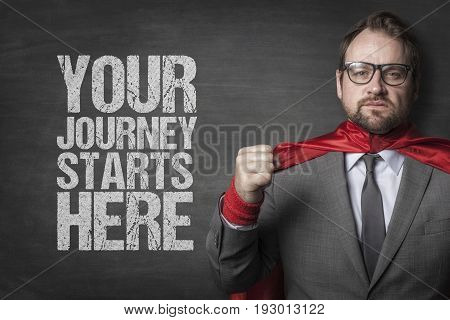 Portrait of determined businessman in superhero cape clenching fist by you journey starts here text on blackboard