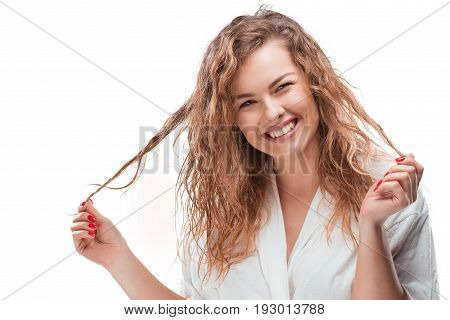Smiling Blonde Woman In White Robe Touching Her Hair Isolated On White