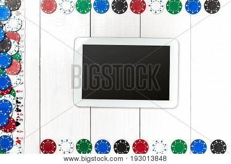 Playing cards, poker chips and tablet on white wooden background. Top view. Copyspace. Poker.
