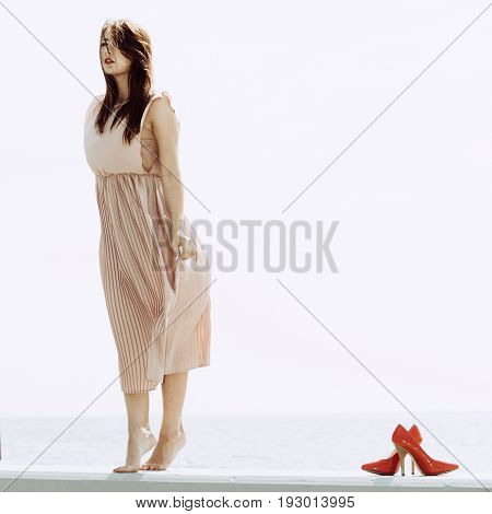 Fashionable clothing fashion and trends concept. Woman in long dress standing and posing barefoot high heels standing next to her.
