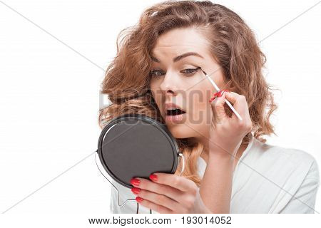 Concentrated Woman Looking At Mirror While Putting Eyeliner Isolated On White