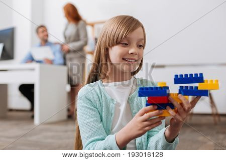 Artistic child. Imaginative cheerful enchanting girl playing with construction set and wanting showing it to her mom who busy working in the office