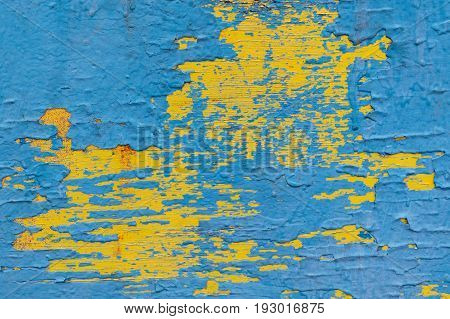 Wooden surface painted with paint in several layers. Paint cracked and peeled off in some places. Paint color blue and yellow. There are streaks and spots of red paint.